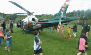 """WOOLWICH CENTRAL SCHOOL students, above, on Tuesday examine a brand-new Lifeflight of Maine helicopter after it landed on the athletic field. Earlier this month, Lifeflight asked elementary students across the state to do drawings of the helicopter — which is nicknamed Whiskey Mike — and share them on Facebook. Lifeflight said the drawing with the most """"likes"""" would win a visit from the helicopter. Fifth-grader Madison Malcolm of Woolwich created the winning drawing, shown on the right, bringing the chopper to the school."""