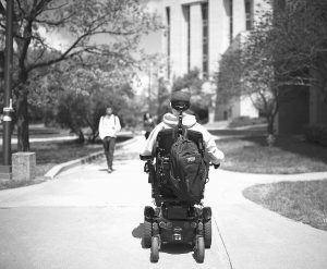 TOM BABB heads toward a marketing class in Haworth Hall on the campus of the University of Kansas after being dropped off by members of the Beta Theta Pi fraternity in Lawrence, Kansas.