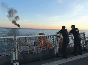 TWO COAST GUARDSMEN watch from the U.S. Coast Guard cutter Stratton as a small fishing boat burns after close to 700 kilograms of cocaine were seized. A few hours later, the Stratton fired its cannon and sank the boat.