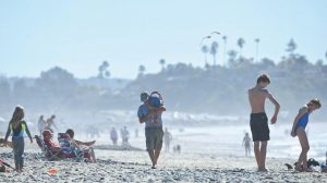 A MAN CARRIES a young boy over his shoulder as he walks among beach goers enjoying unusually warm winter temperatures in Encinitas, California. Global warming's milder winters will likely nudge Americans off the couch more in the future, a rare, small benefit of climate change, a new study finds.