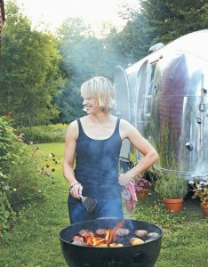 THIS PHOTO shows Erin French, owner of The Lost Kitchen restaurant in Freedom, Maine, grilling burgers with an Airstream trailer in the background.
