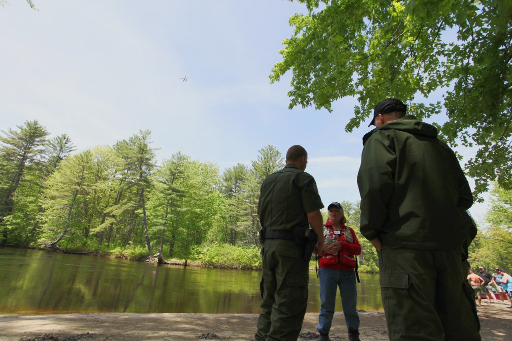 Yvette Lizotte of the American Red Cross talks with game wardens at the Walker's Falls Campground during the search for a missing woman on the Saco River in Fryeburg on May 28. A Fryeburg officer who was injured during the search has died.