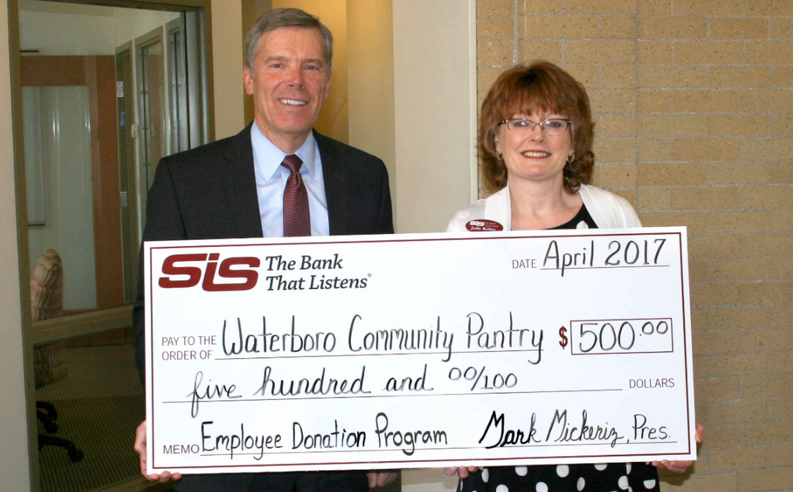 SIS Bank President and& CEO Mark T. Mickeriz, left, presents a check to Julie Kelley, a SIS employee and a volunteer at the Waterboro Community Pantry. SUBMITTED PHOTO