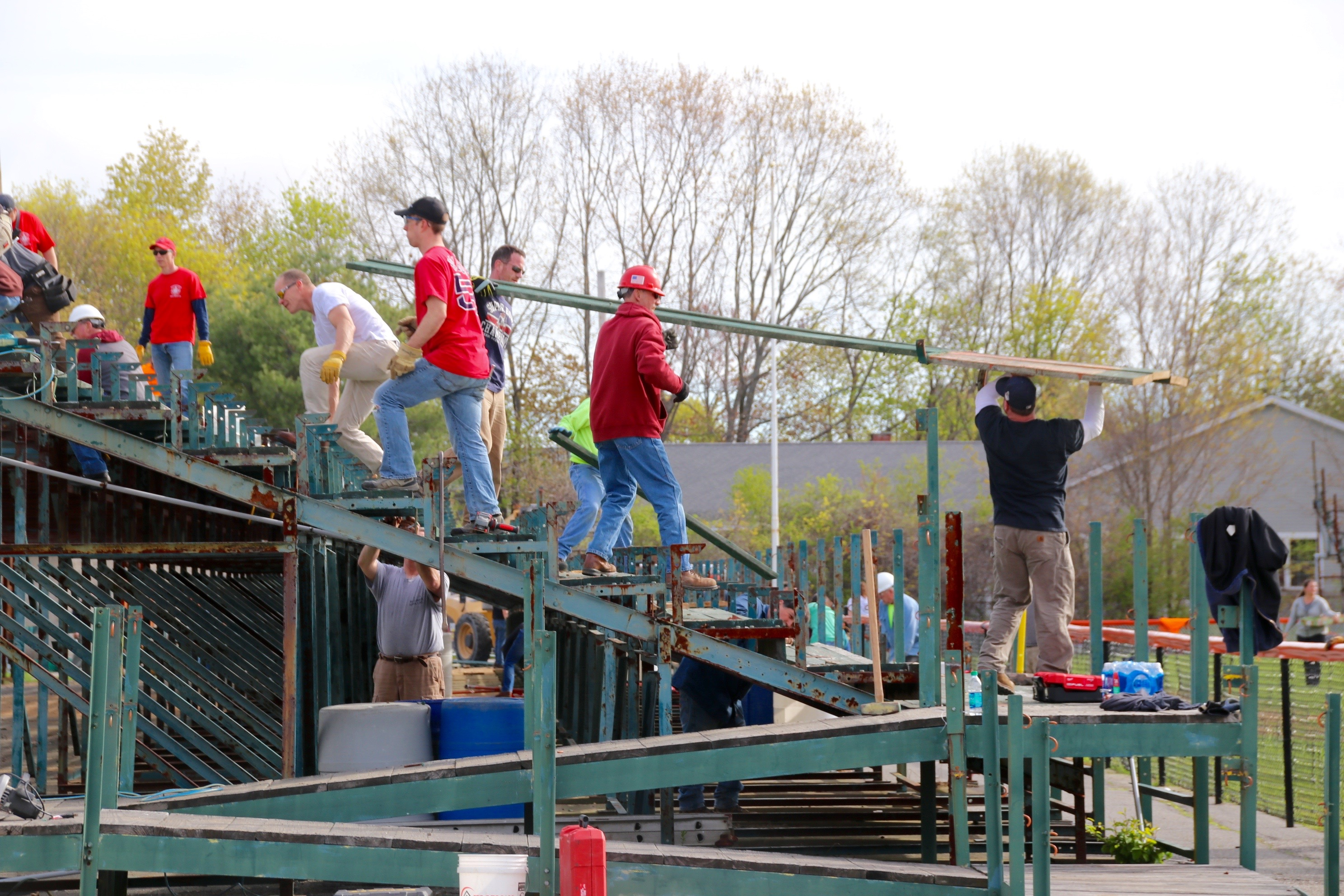 Many hands make light work, as evidenced by this community effort to remove worn out and unsafe bleachers from Biddeford's Waterhouse Field. About  200 people gathered to do their bit to help the Waterhouse Field Alumni Association get it done. TAMMY WELLS/Journal Tribune