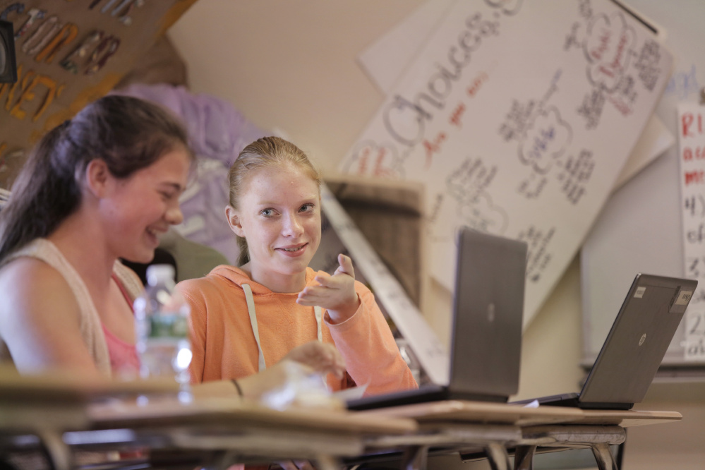 "Nokomis Regional High School freshman Kylee Elderkin, right, speaks with classmate Sierra Robichaud while the two work on an assignment in their English class at the Newport school recently. ""I definitely would have struggled"" in algebra, Elderkin says, if she hadn't been allowed to retake tests on elements she hadn't yet mastered."
