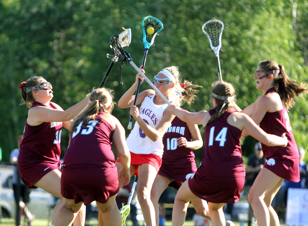 Messalonskee's Ally Turner tries to get a shot off as Windham defenders converge in the first half of the Class A North championship game Wednesday at Thomas College. Messalonskee won in overtime, 7-6.