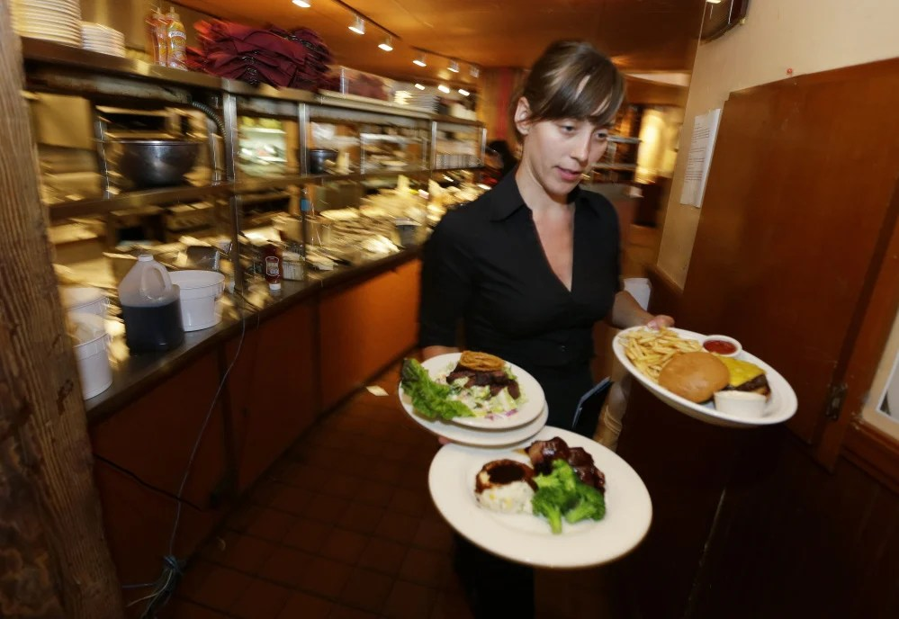 A waitress at a Seattle restaurant carries food to a table in 2014. A new study finds that low-wage workers may not benefit overall from an increase in the minimum wage, but the study does not include larger employers.