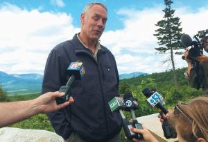 U.S. INTERIOR SECRETARY Ryan Zinke talks with reporters with part of Mount Katahdin in the background at the Katahdin Woods And Waters National Monument near Stacyville on Wednesday.
