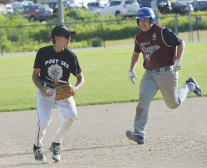 POST 202 THIRD BASEMAN Coenradt Taylor, left, looks to first base after forcing Rogers Post base runner Derek Wolverton at third base during a Junior American Legion baseball game in Topsham. Post 202 won, 6-3.