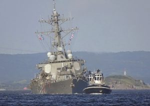 The damaged USS Fitzgerald is being towed by a tugboat in the waters near the U.S. Naval base in Yokosuka, southwest of Tokyo, after the U.S. destroyer collided with the Philippine-registered container ship ACX Crystal in the waters off the Izu Peninsula Saturday. Crew members from the destroyer USS Dewey were helping stabilize the damaged USS Fitzgerald after its collision off the coast of Japan before dawn Saturday, leaving seven sailors missing and at least three injured. (AP Photo/Eugene Hoshiko)