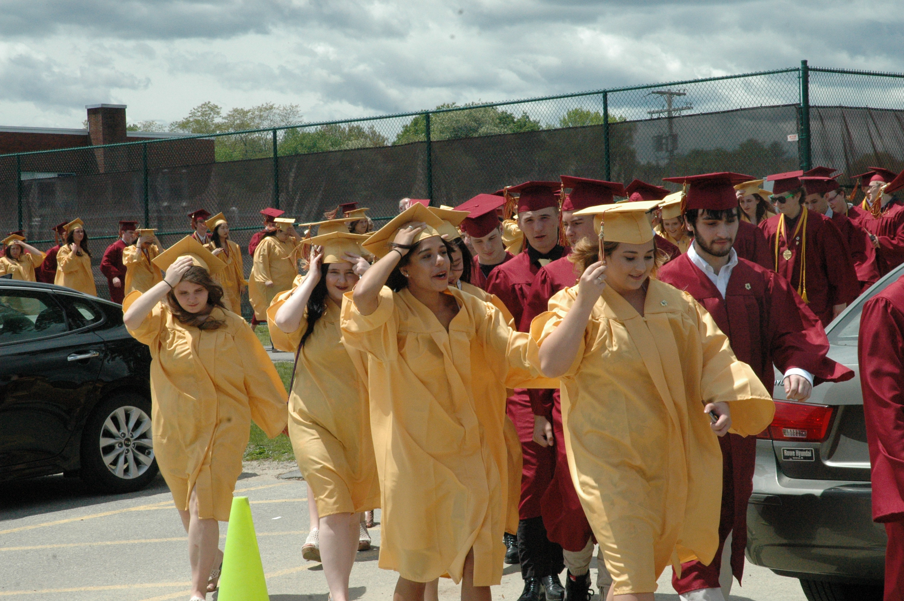 Graduating seniors at Thornton Academy hold on to their caps as wind blows through the campus on Sunday.LIZ GOTTHELF/Journal Tribune