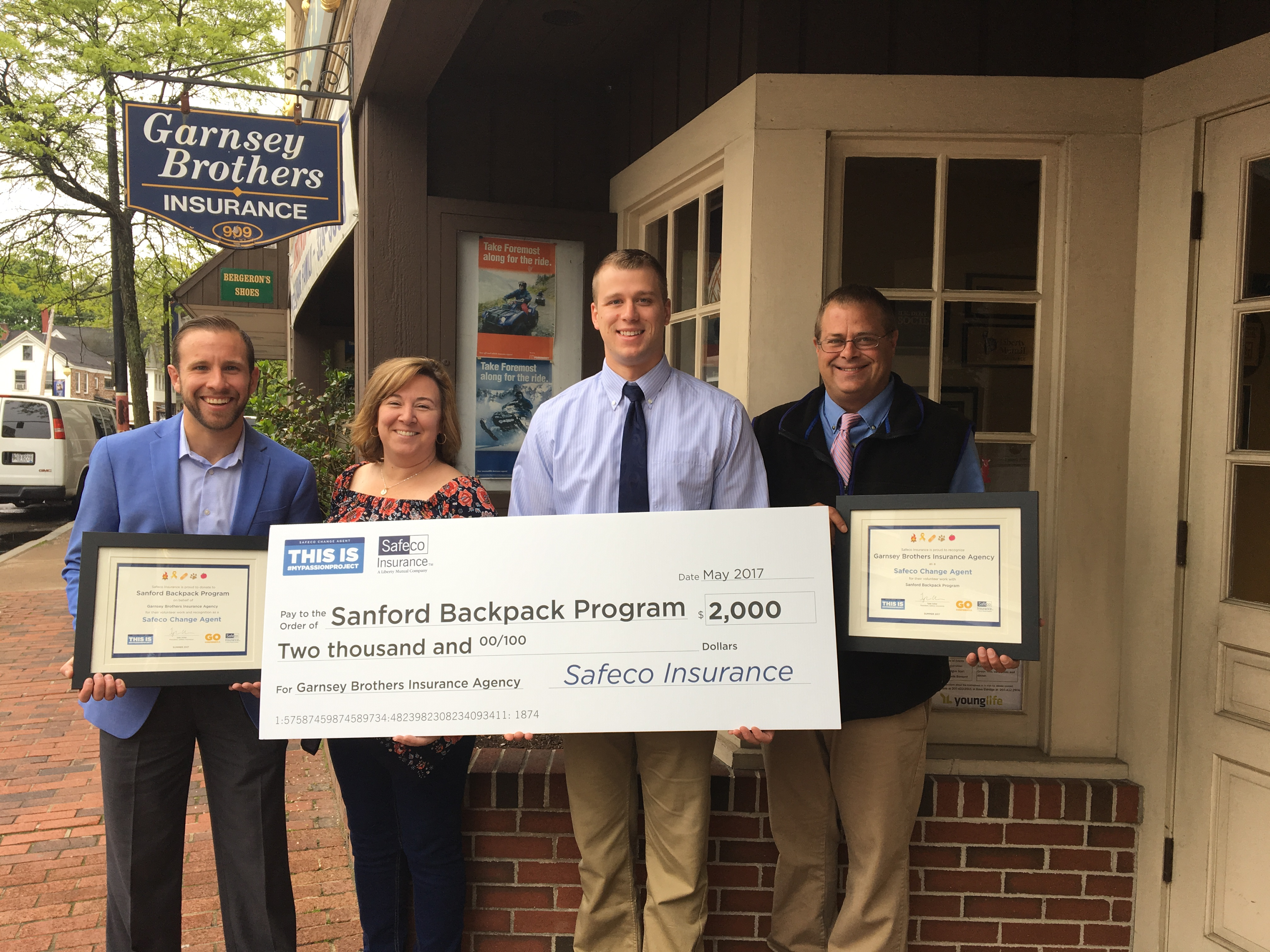 Nate Maclure  OF Safeco Insurance, Kirsten McGarry of the Sanford Backpack Program and Nick Roux and Keith Lapointe, both of Garnsey Brothers Insurance Agency pause for a photo commemorating the donation by Safeco Insurance to the Sanford Backpack Program through the efforts of Garnsey Brothers in a social media campaign. COURTESY PHOTO/Strategies for a Stronger Sanford