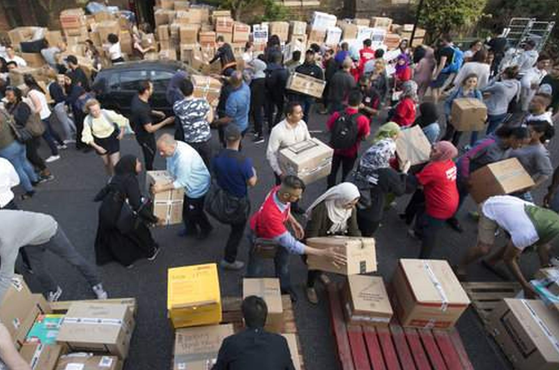 Voluneers organize donations near Grenfell Tower in west London, Thursday, June 15, 2017. A massive fire raced through the 24-storey high-rise apartment building in west London early Wednesday, and London fire commissioner says it will take weeks for the building to be searched and 'cleared'. (AP Photo/Tim Ireland)