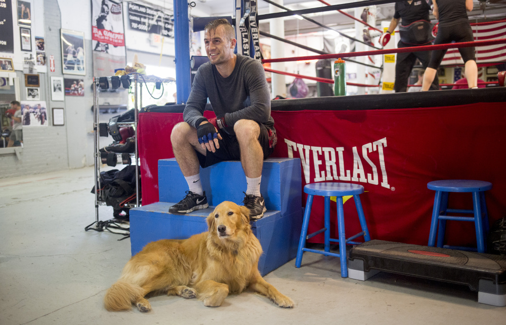 PORTLAND, ME - JULY 27: Jason Quirk rests between rounds with his dog, Abbey, while training for a fight he has on Saturday at the Portland Boxing Club. Quirk, who is from Scarborough, has been training actor Patrick Dempsey in boxing since June. He has been boxing at the Portland Boxing club since he was 15 years old. (Staff photo by Brianna Soukup/Staff Photographer)