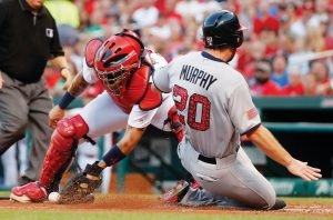 WASHINGTON'S DANIEL MURPHY (20) scores as the throw gets away from St. Louis Cardinals catcher Yadier Molina during the third inning of a baseball game on Sunday in St. Louis. The Nationals won, 7-2.