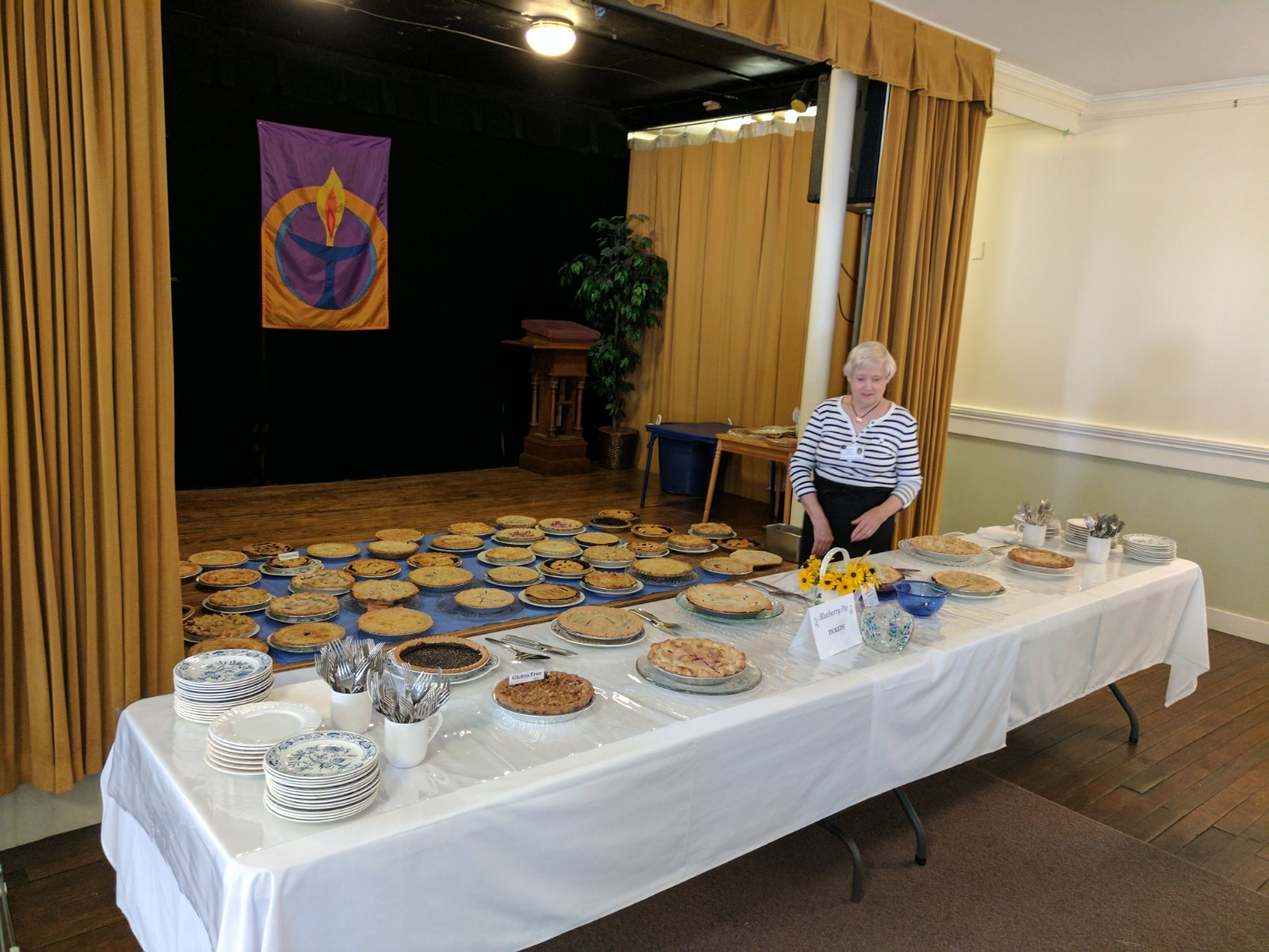 Festival organizer Susan Jack stands among dozens of blueberry pies baked by volunteers for the Blueberry Festival in Kennebunk on Saturday. RYDER SCHUMACHER/Journal Tribune