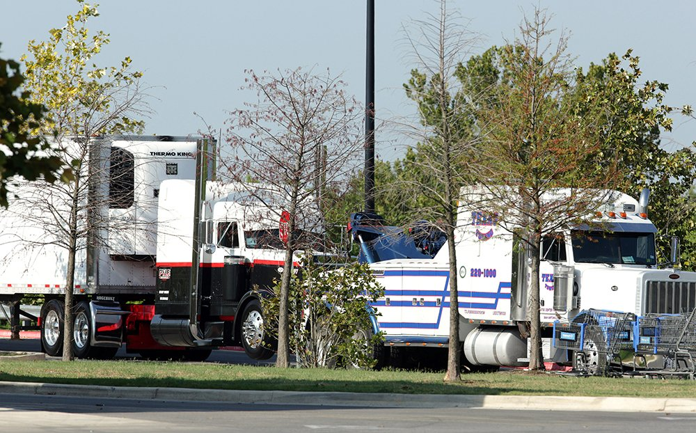 Police prepare to tow a tractor-trailer Sunday in which 10 people believed to be illegal immigrants being smuggled into the United States were found dead.