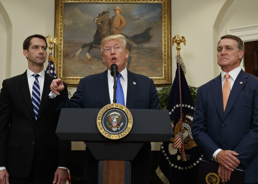 At the White House on Wednesday, President Trump talks about legislation sponsored by Sen. Tom Cotton, R-Ark., left, and Sen. David Perdue, R-Ga., to reduce legal immigration.