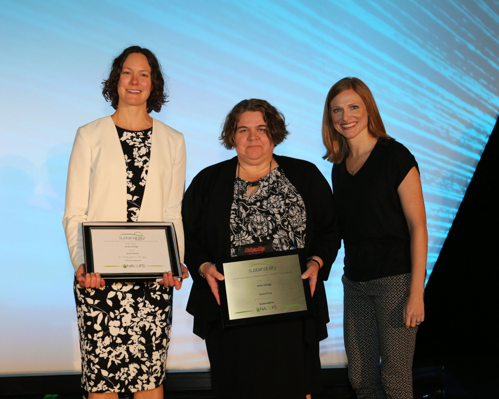 Jennifer deHart, left, chief sustainability officer at Unity College, and Lorey Duprey, middle, director of dining, accept the grand prize for sustainability from a representative of the National Association of College and University Food Services at the group's conference in July in Nashville, Tennessee.