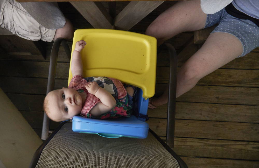 6-month-old Sydney Renda of Massachusetts looks up at a visitor while eating dinner with her parents on the porch of a vacation home in Ocean Park.