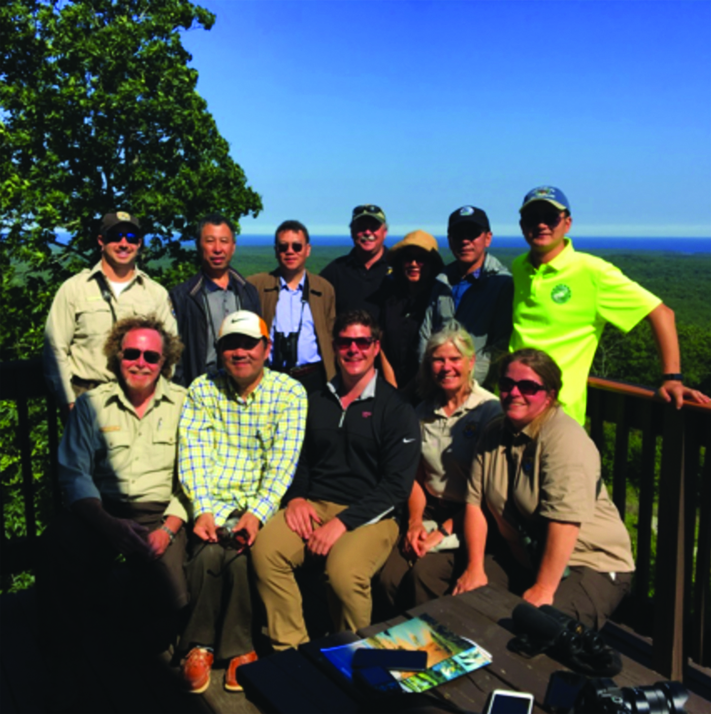 Staffers at Rachel Carson Wildlife Refuge and Chinese delegates sit atop the summit of Mount Agamenticus. RYDER SCHUMACHER/Journal Tribune
