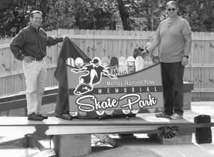 SETH BERRY, LEFT, and Bowdoinham selectman Tony Lewis unveil the new sign for the Matthew Townsend Parker Memorial Skatepark at a dedication ceremony in Bowdoinham on Friday.