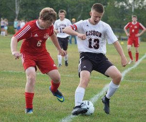 LISBON'S NOAH AUSTIN (13) looks to get past the defense of Wiscasset's Matt Martin in MVC boys soccer on Friday.