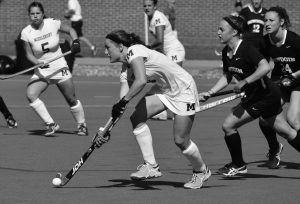 BOWDOIN'S LAURA COOPER, center, looks to move the ball during a NESCAC field hockey clash with Middlebury on Saturday.