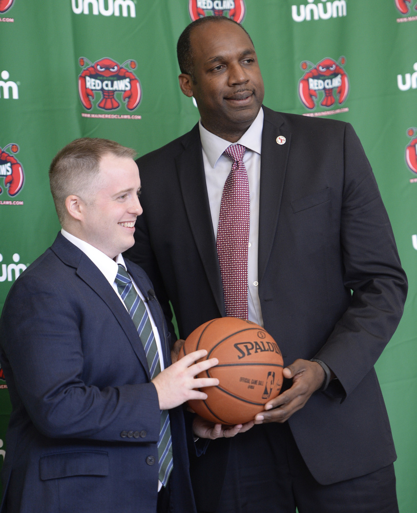 Brandon Bailey, left, the new coach of the Maine Red Claws, poses for photographs Thursday with Dajuan Eubanks, the team president. Bailey was the Boston Celtics' video coordinator since 2011.
