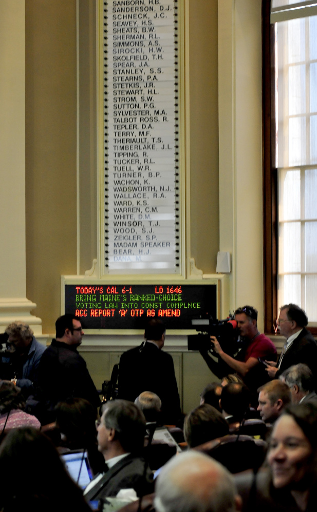 Members of the media assemble beneath a malfunctioning electronic vote tally board, one reason for delays during a special session of the Legislature in Augusta on Monday.