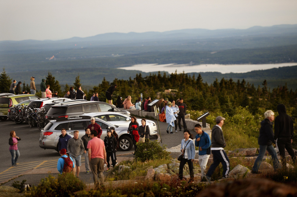 Hundreds flock to Cadillac Mountain in Acadia National Park on a late-July day to see the sunrise. The National Park Service has proposed raising entrance fees at Acadia and 16 other parks to generate revenue to reduce the backlog in maintenance and infrastructure projects at the sites.