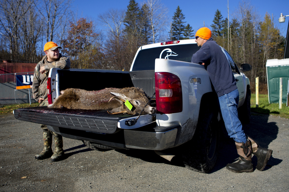 Kevin Wilkes, left, and Chris Withee wait for the deer that Tia Withee shot to be tagged Saturday at Jim's Variety in Athens.
