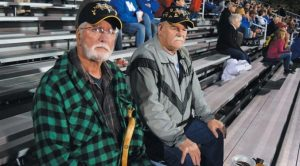 BATH-BORN VETERANS Walter Coombs and John Williams sit in the bleachers at McMann Field, waiting for the game between Freeport and Morse High to begin.