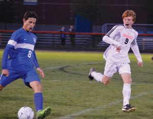 MT. ARARAT'S MAXIMO VARELA (8) is about to send a pass forward past Brunswick's Lane Foushee (9). The Eagles and Dragons played to a 2-2 KVAC deadlock in blustery Brunswick on Monday in the regular-season finale for both teams.