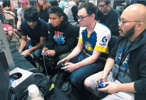 """CONNOR NGUYEN, at right, and Griffin Williams, second from right, compete in a """"Super Smash Bros. Melee"""" tournament at the Shine eSports festival at the Seaport World Trade Center in Boston. Williams, 21, is captain of an esports team at the University of California, Irvine, and Nguyen, 23, is a graduate of the school. The University of California, Irvine, is among a growing number of U.S. schools starting to offer at least partial scholarships to students who compete in esports, competitive video-game playing."""