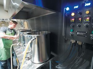 """KAL WALLNER looks over his kettles in his home brewery room in Ottawa, Canada. Wallner is an electrical engineer who designed a brewing system for himself that he now sells online at TheElectricBrewery.com. With an electric system, """"you can brew indoors in your flip-flops,"""" says Wallner."""