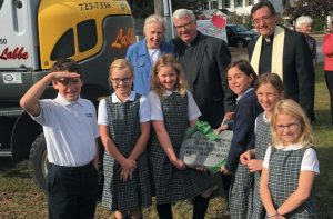 THIRD GRADERS in Mrs. York's class, Wyatt, Eliza Davies, Abbie Minzer, Aurora Blier, Tessa Couture and Maddie Smith present a stone plaque to front back, from left, Sister Angela Krippendorf, Rev. Tom Murphy and Rev. Frank Murray.