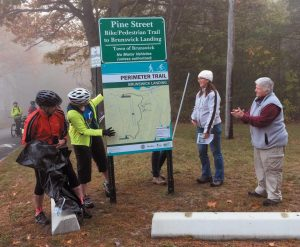 TOM BRUBAKER, Melissa Fochesato, Angela Twitchell and Kathy Wilson, from left, unveil the new sign for the Brunswick Landing Perimeter Trail Saturday.