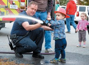 MARLEY LOWE, 2, sprays water from a fire hose with help from Brunswick firefighter Pete Merrow during the annual open house at Emerson Station in Brunswick Wednesday. The open house is one of several held by local fire departments in order to mark fire prevention week.