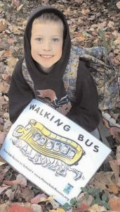 KALAN, in third grade, waits for his friend to get off the bus Friday before the walk to school.
