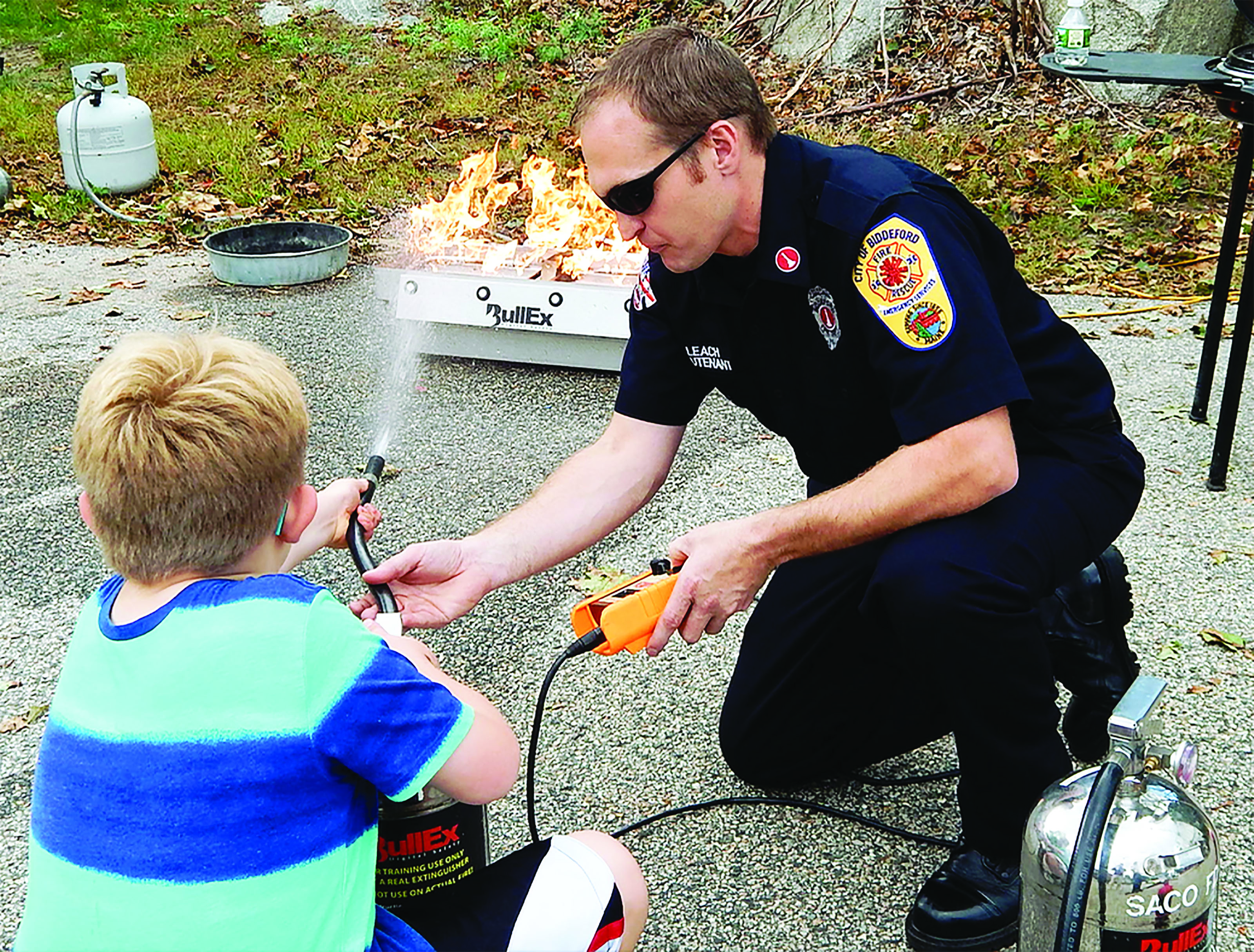 Biddeford Fire Department Lt. Matthew Leach shows a student how to properly use a fire extinguisher during the fire department's annual open house held at the Biddeford Fire Station on Saturday. ED PIERCE/Journal Tribune