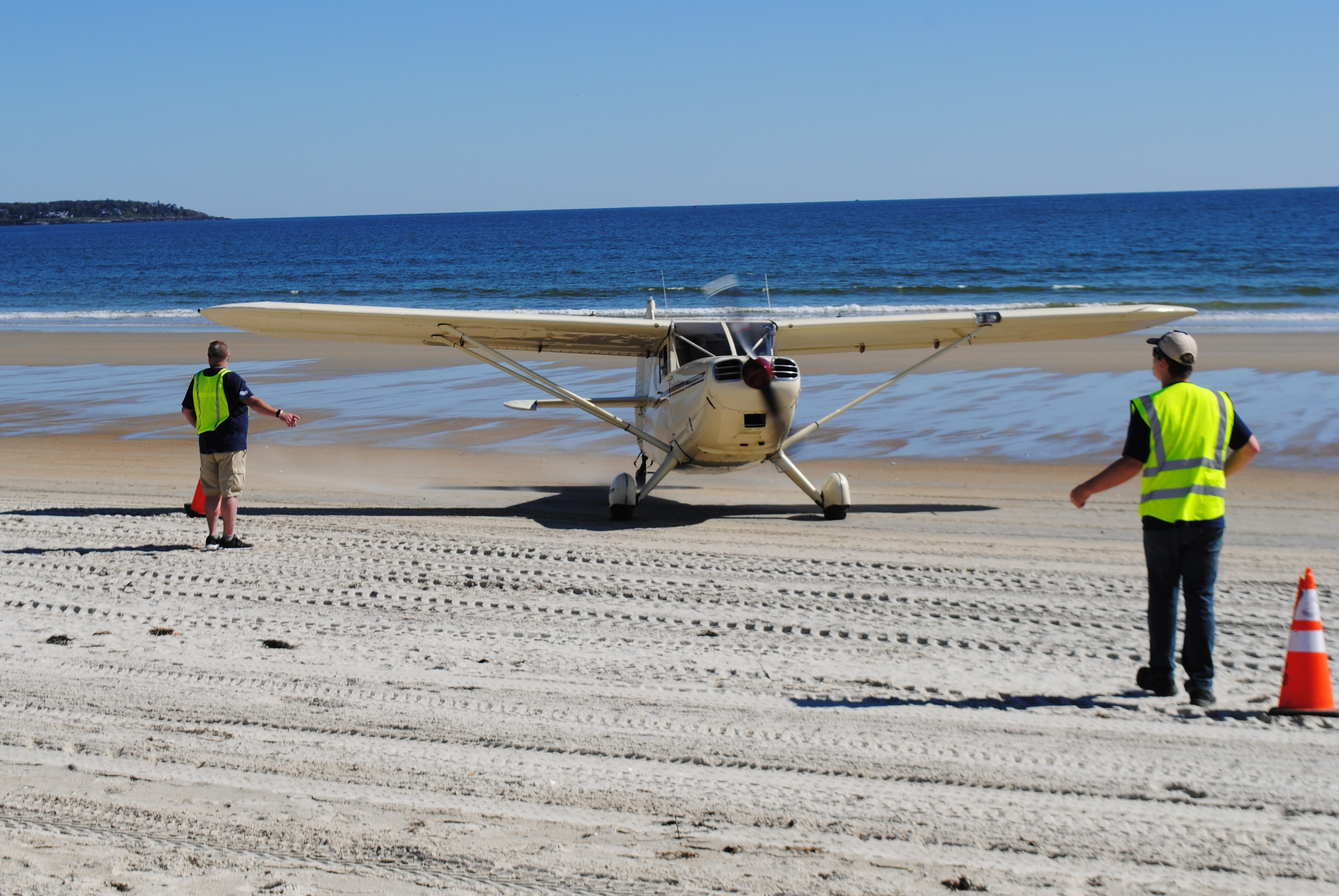 OOB365 member Israel Collins and Wings 4 Wishes organizer Chase Walker direct a plane on to the beach in Old Orchard Beach on Sunday. LIZ GOTTHELF/Journal Tribune