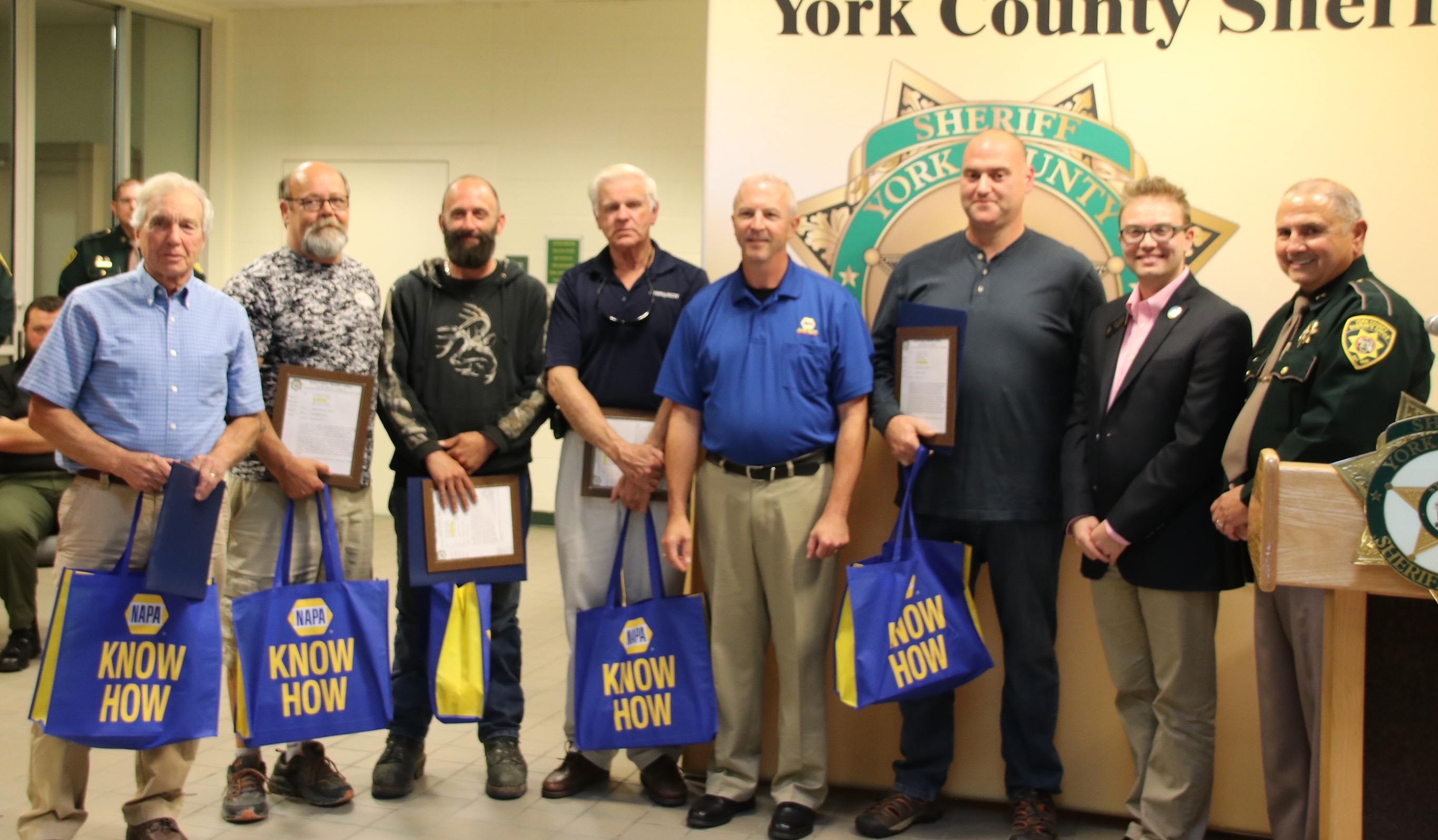 Five men who rescued a woman from a burning car in Limington in August were recognized by the York County Sheriff's Office and area Legisaltors on Friday — and were given thank you gifts by NAPA Auto Parts. Here, left to right, are rescurers Joe Parent, Mark Cable, David Tetreault and Donald Corbett, NAPA manager Rob at Lind, rescurer Timothy Paquette, Sen. Justin Chenette and Sheriff bill King.