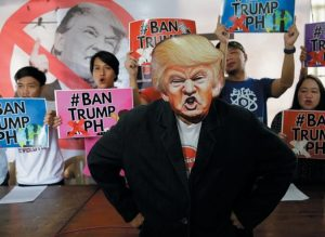 A FILIPINO PROTESTER wearing a mask of U.S. President Donald Trump stands in front of other activists holding slogans during a press conference to announce their protest plans in metropolitan Manila, Philippines this morning.