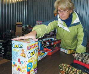 PHYLLIS THIBOUTOT stuffs a box full of toys that will soon go to a Midcoast family to help make Christmas a little brighter for children who may not get presents otherwise.