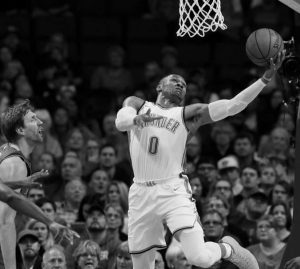 OKLAHOMA CITY THUNDER guard Russell Westbrook (0) shoots as Dallas Mavericks forward Dirk Nowitzk (left) looks on in the first quarter of an NBA basketball game in Oklahoma City on Sunday. The Thunder won, 112-99.