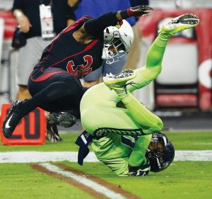 SEATTLE SEAHAWKS wide receiver Paul Richardson makes the catch as Arizona Cardinals safety Budda Baker, left, defends during the first half of an NFL football game on Thursday in Glendale, Ariz. The Seahawks won, 22-16.