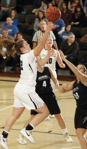 BOWDOIN'S ABBY KELLY (22) goes to the basket over UNE defenders Sam MacDonald (10) and Kristine McNall (4).
