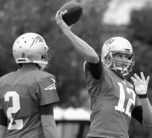 NEW ENGLAND PATRIOTS quarterback Brian Hoyer (2) stands by as starting quarterback Tom Brady (12) passes the ball during an NFL football practice on Wednesday in Foxborough, Mass. The Patriots have signed former 49ers quarterback Hoyer to be Brady's backup.
