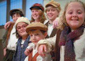 STREET URCHINS in the Chocolate Church's theatrical production of Scrooge! From left front row: Sadie Daniels, Ethan McDonald, Evelyn Ringrose. From left back row: Isaac Ensel, Samantha Melquist, Cayden Green